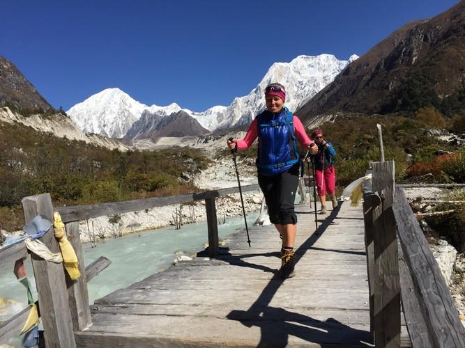 trekkers crossing the bridge of the route to Manaslu trek